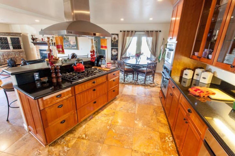 Kitchen & bistro nook w/granite counters, travertine floor & open to living room