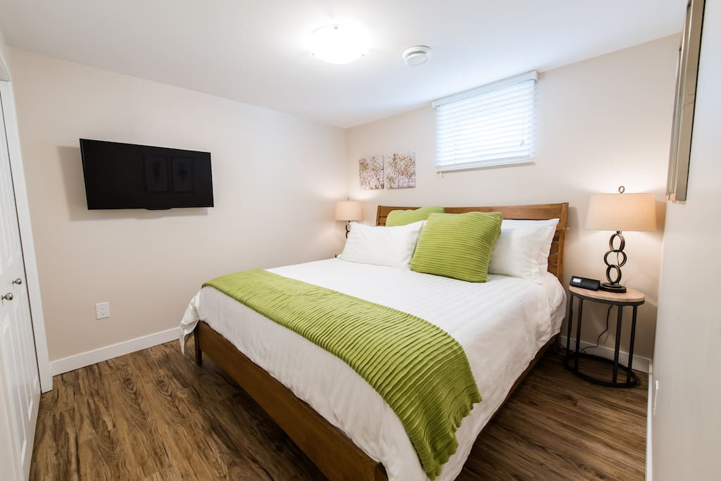 """Bedroom #2 with king bed and 39"""" Roku TV on a swivel mount.  Watch TV while lying in the comfy bed."""