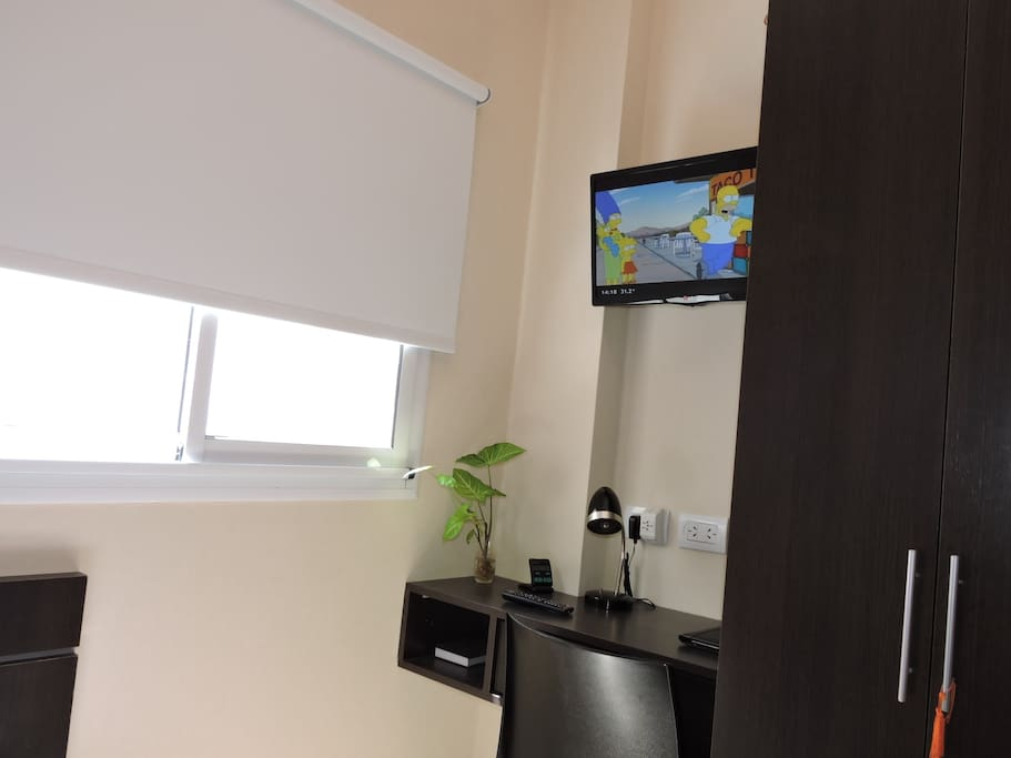 View of room with cable TV and working desk