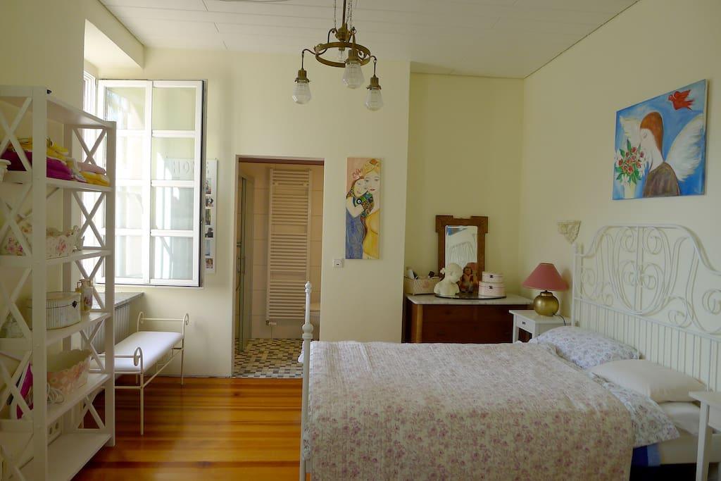 Gemütliches und ruhiges Schlafzimmer mit Regal, großem Spiegel und Kleiderschrank