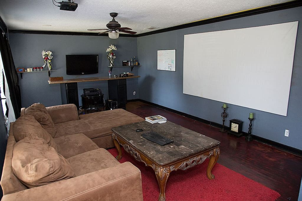 The front living room includes a mammoth projection television system, killer overhead speakers and bar area to get the party started and keep it going late into the night