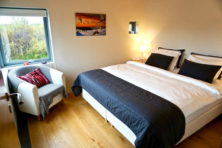 Main House. Bedroom 2 with a high standard bed and a mountain view
