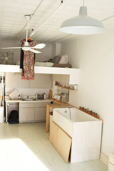 view of the loft with the bed and below the bath tub and kitchen