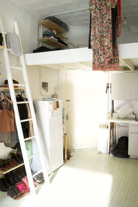 view of loft and clothing rack and fridge and door