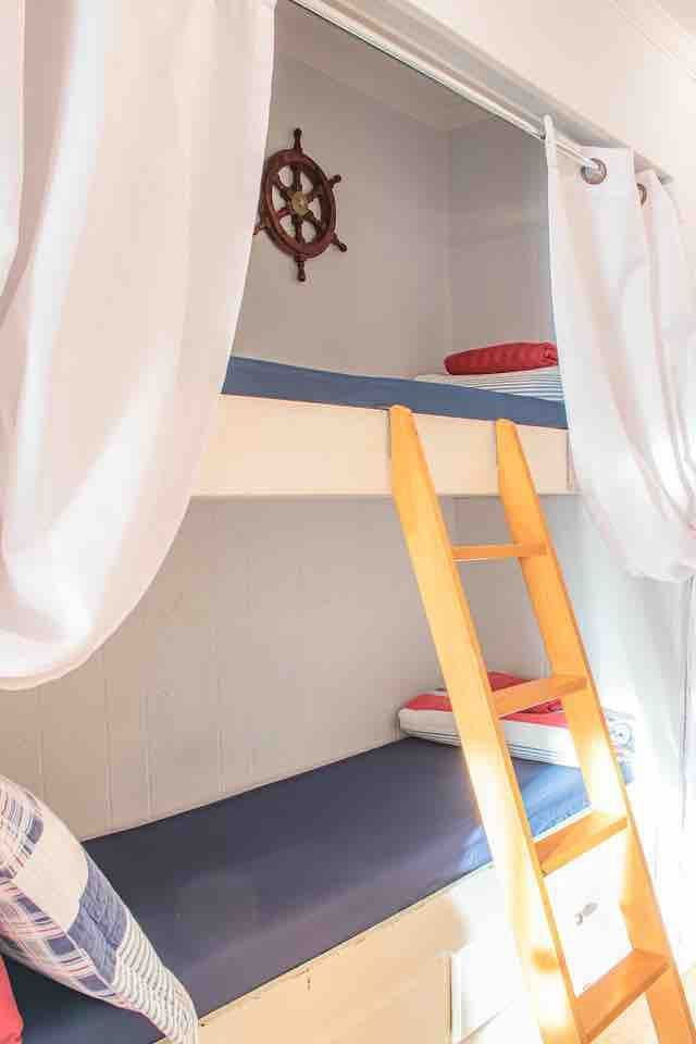 Bunks beds are in the hallway near the main bedroom, ladder and safety rail are provided