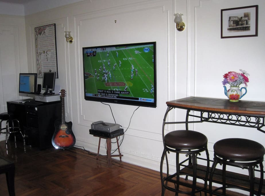Desk, Large Flat Screen TV with cable, & Breakfast Bar with Wine Rack on wall opposite the sofa.