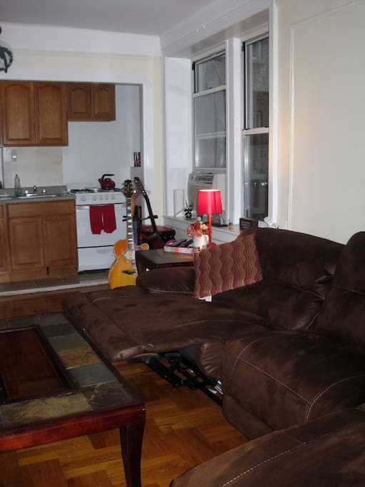 Large Living Room with Kitchenette on one wall. Oversized sofa has recliner built into one side... perfect for watching TV.