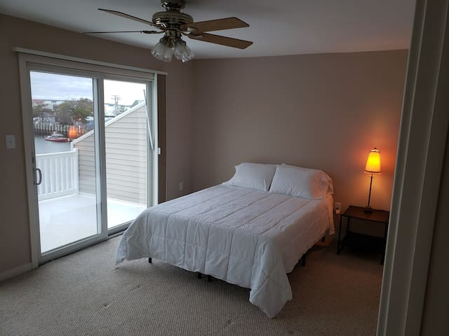 Master bedroom with a queen size bed and two sliding doors with access to balcony.