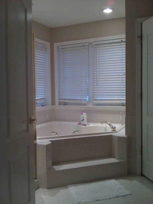 Gorgeous private bathroom with a large corner Jacuzzi and separate shower