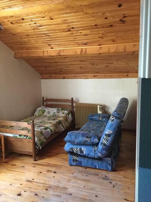 Un lit une place et un canapé clic-clac pouvant être utilisé comme lit d'appoint