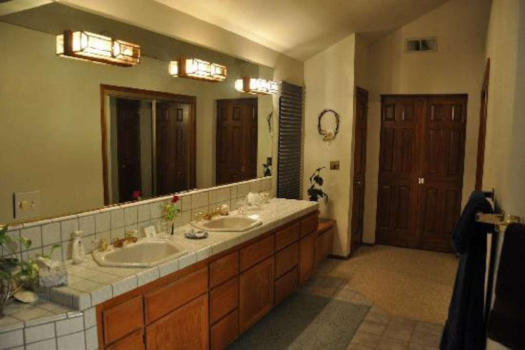A private bathroom contains double sinks, a sunken tub and a walk in tiled shower.