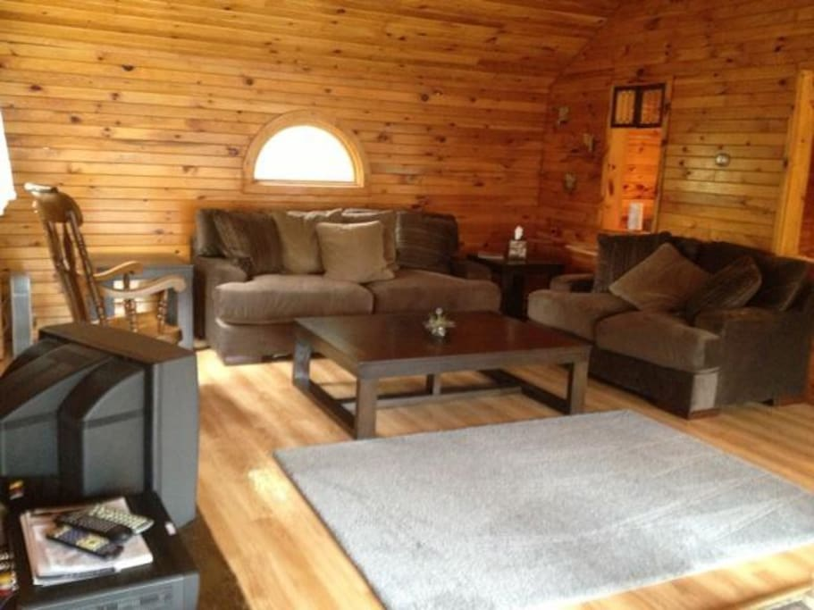 Upstairs living room has a cozy, rustic feel and looks out over primary deck and lake.