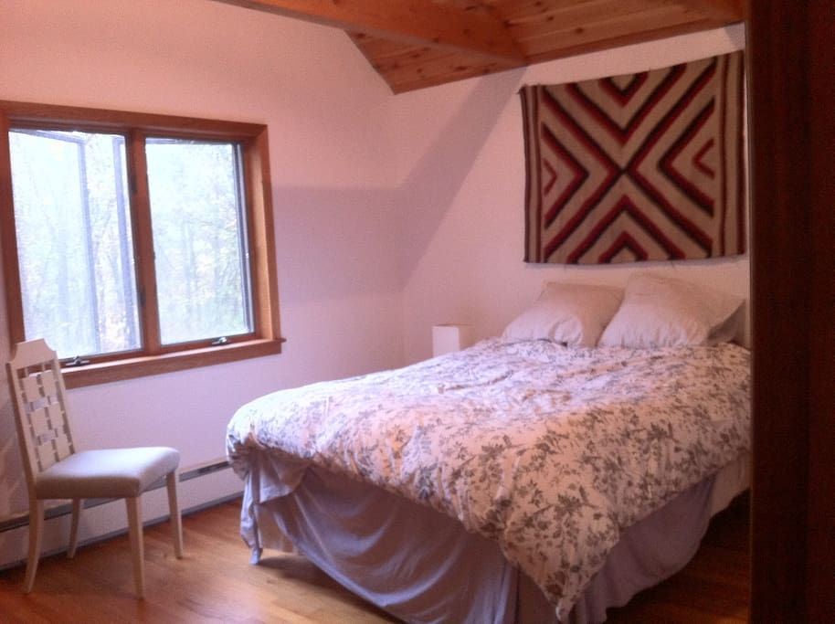 master bedroom on the second floor featuring vaulted ceilings and antique navajo rugs