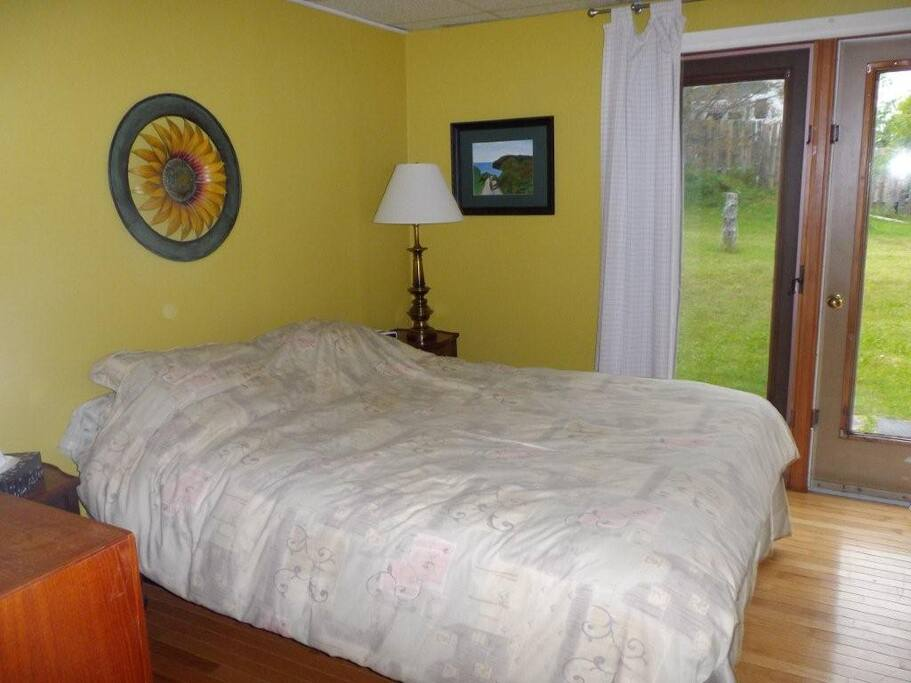 your bedroom with queen bed and french doors to huge yard