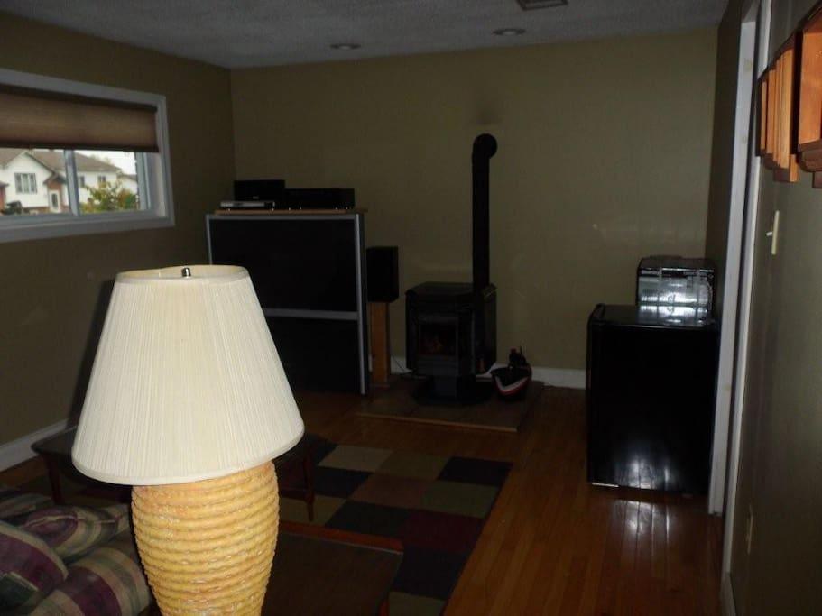 living room , pellet stove , large screen TV, plus more