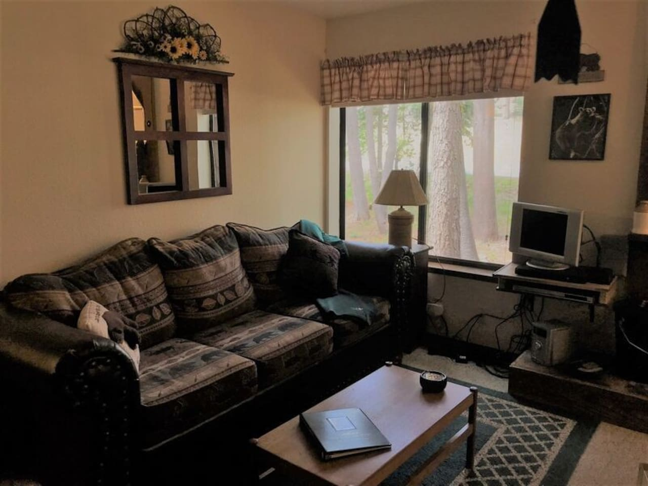 Large comfortable couch, perfect for enjoying the tree view in summer, or cozy up by the wood fire in winter!