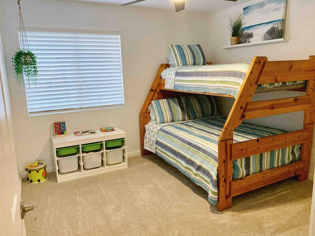 Study solid wood bunkbeds with full size mattress on the bottom and twin size mattress on top.  Chest is full of toys for young children.  There is a queen sized air mattress in the closet, along with highchair, and Bumbo seat for infant/toddler.