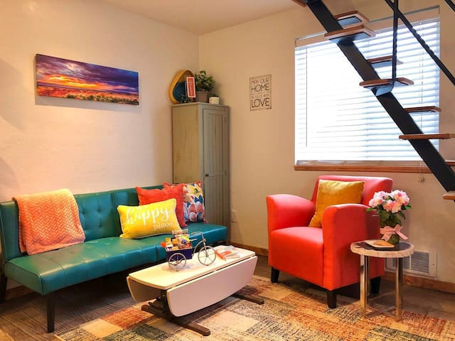 Warm inviting livingroom space with the third bed, a single futon.  A foam egg crate, sheets, pillow and blanket are tucked behind it.