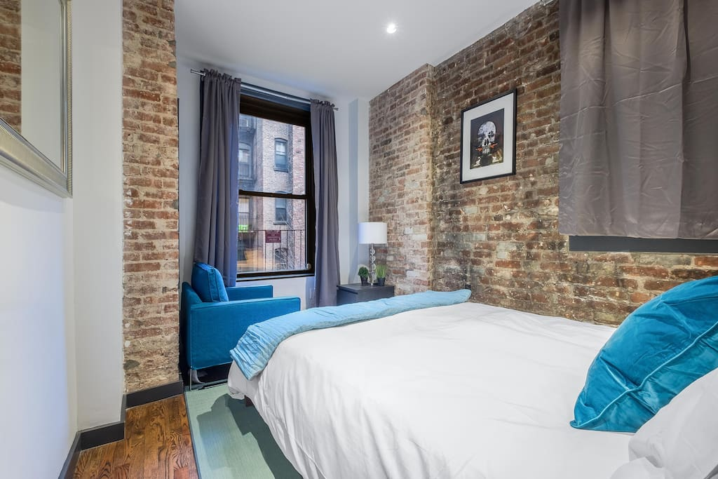 Beautiful brick exposed room with comfy bed and natural light