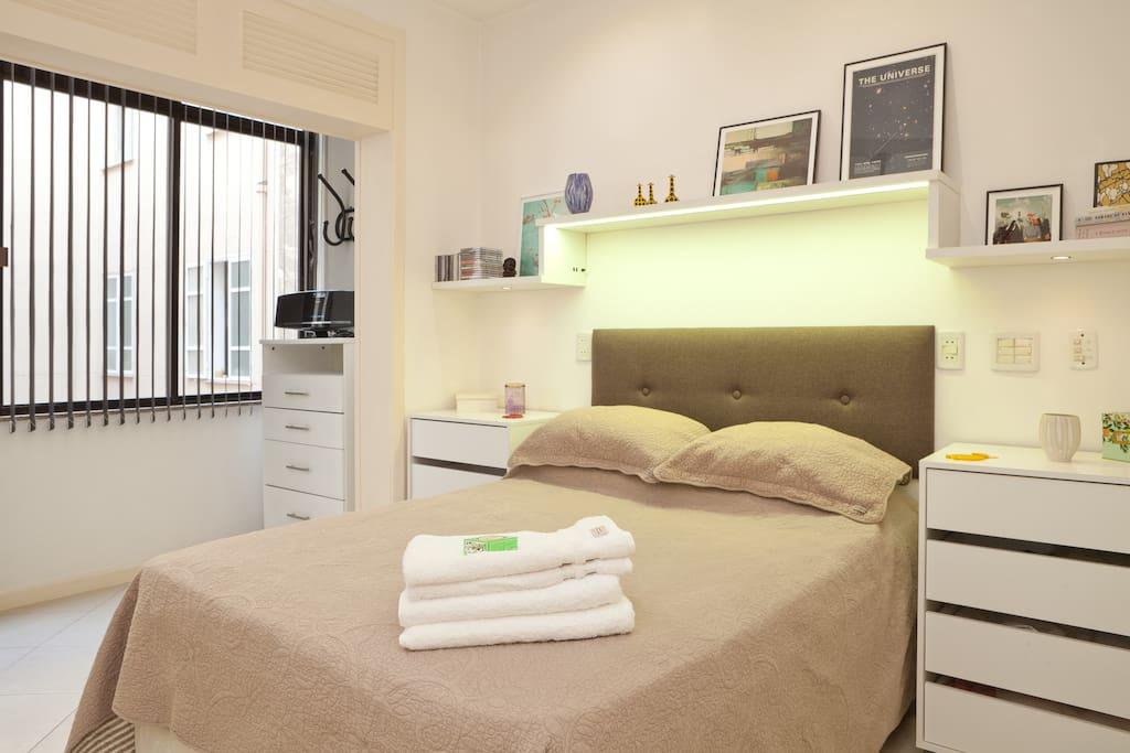 Very comfortable double bed in large, bright and spacious room. / Cama de casal em quarto espaçoso e arejado.