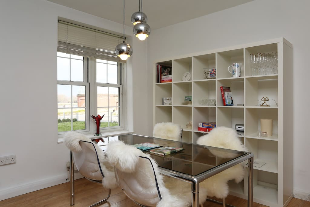 Vintage glass table and lighting meets modern chairs and plush sheepskins