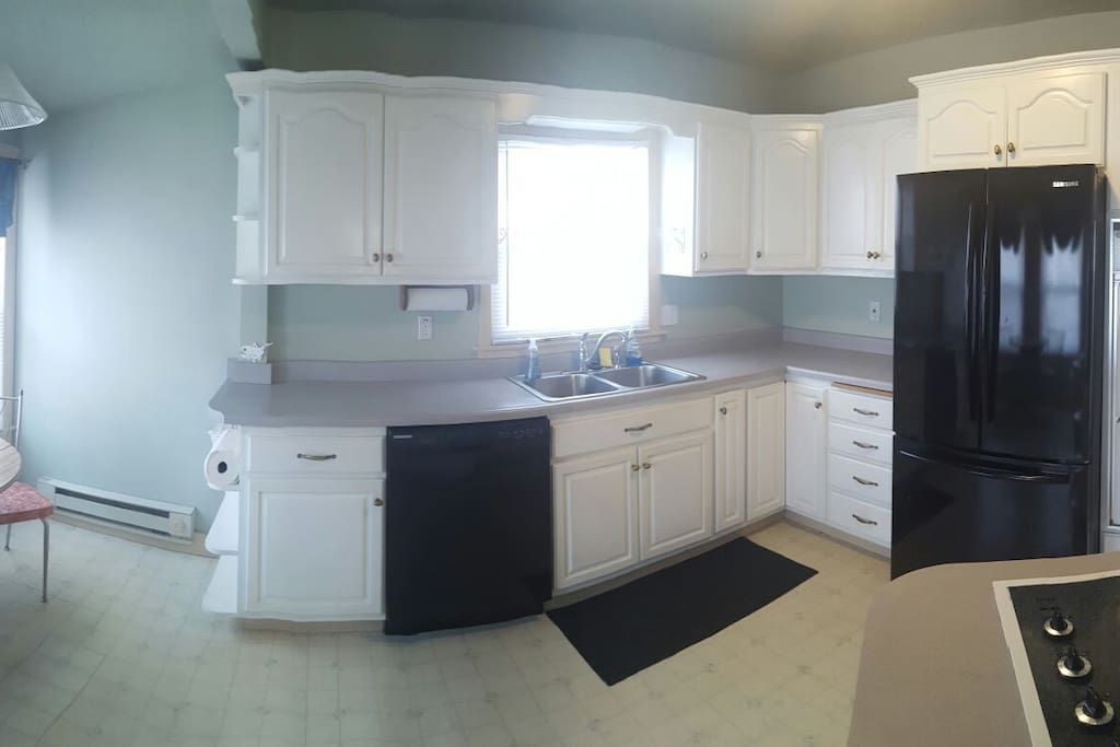 Kitchen with small breakfast nook.  Plates, flatware, cups, utensils, pots, pans, stove, oven, microwave, toaster, and fridge available for use.
