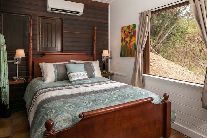 queen bed with picture window overlooking the hills above Turner Bay