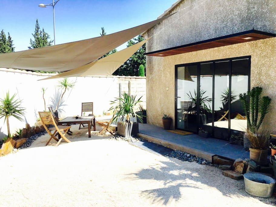 Extérieur de la maison avec une petite terrasse en bandeau et un salon de jardin sous les toiles d'ombrage.