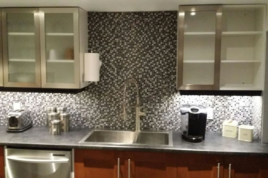 Restaurant style kitchen hand spray and double stainless sinks. A Kuerig is provided with the essential coffee and teas. Also provided is staples like pasta and rice.