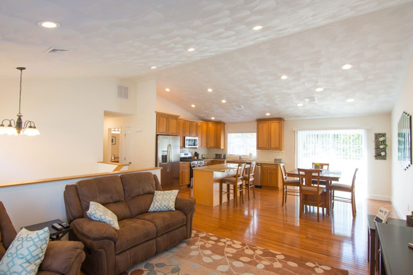 The modern, open floor plan with living room, dining room, and kitchen.  Off the dining room is a large, private deck. All three living room seats are full recliners.