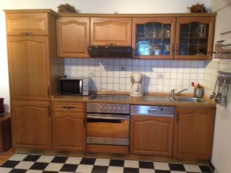 Küche mit Mikrowelle, Backofen, Herd, Kühlschrank, Spülmaschine