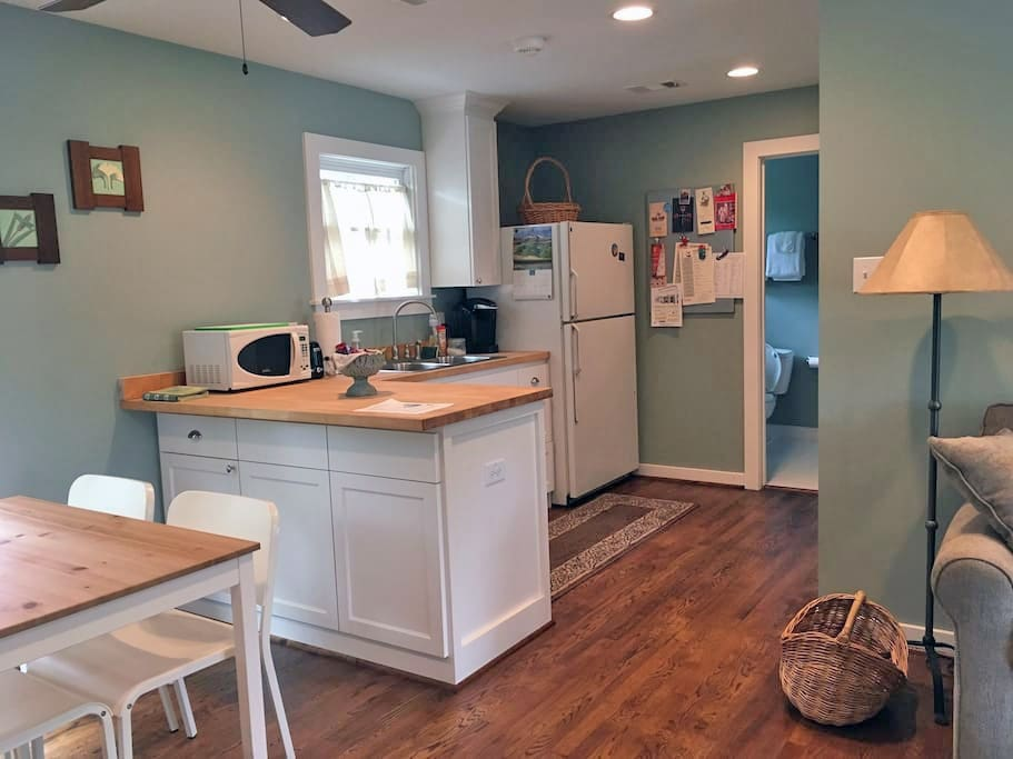 Kitchenette with microwave, refrigerator, Keurig coffee maker and electric skillet. Stocked with utensils, glasses, cups, plates and bowls. Separate dining area to left.