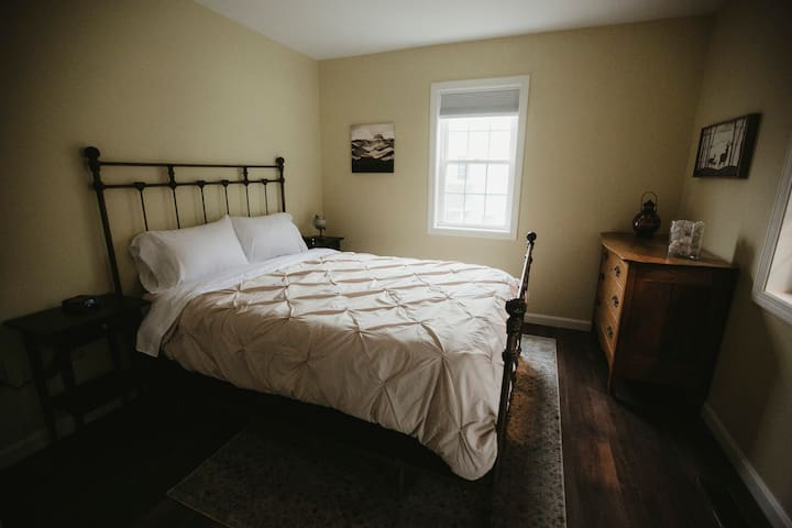 The main floor bedroom has an antique brass queen bed and a full bathroom across the hall