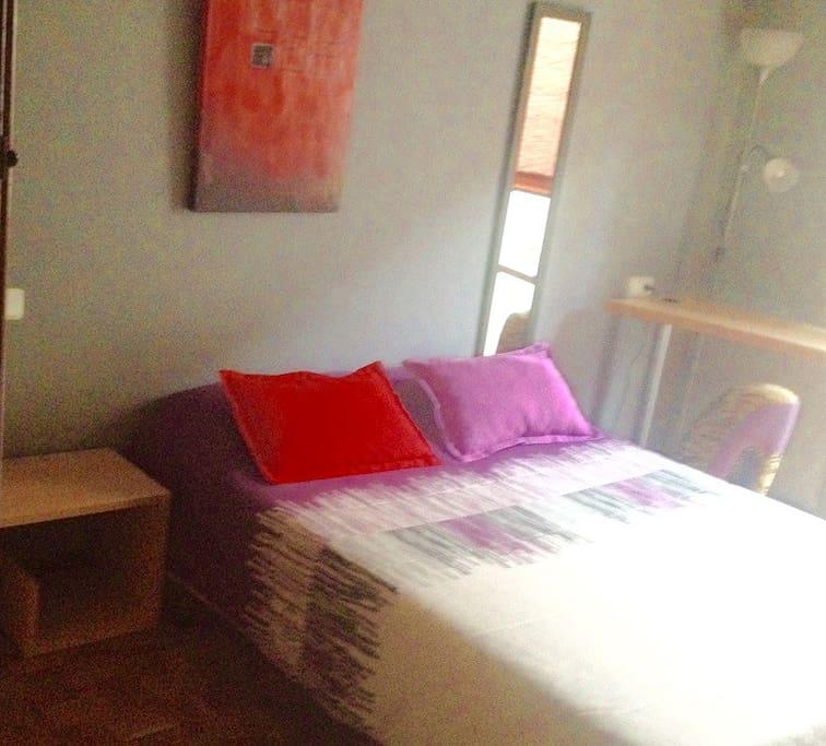 Habitación amplia y luminosa. Cama de 135cm con mesilla a un lado y espejo al otro.