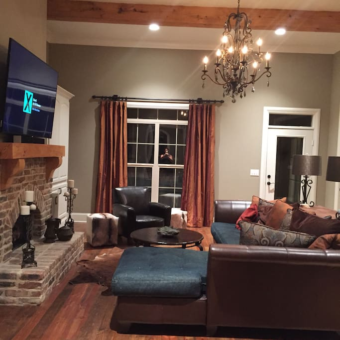 Living room with fireplace and 70 inch TV.