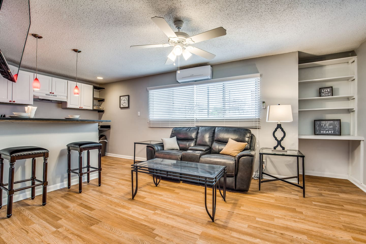 This living area is right off the entryway. Here you can see the complete kitchen with bar stools for dining. The room is complete with a ductless AC/Heating unit and a modern ceiling fan to accommodate you in any weather. Powered by a remote.