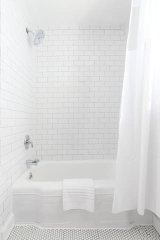 Newly-refreshed shower and bath with subway tile and rain shower hardware.
