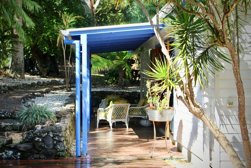 French doors open to the patio surrounded by tropical garden
