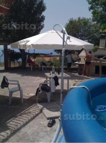 La foto mostra giardino privato con forno barbecue e piscina fuori terra con tavolini sdraio e sedie.  Garden with bbc, Wood own, pool
