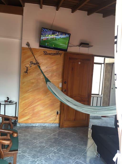 Zona común con sofa, hamaca y tv
