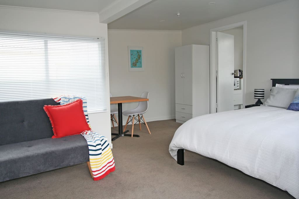 Bedsit/lounge area with queen bed, sofa couch, table and chairs, wardrobe, TV and WiFi throughout cottage.
