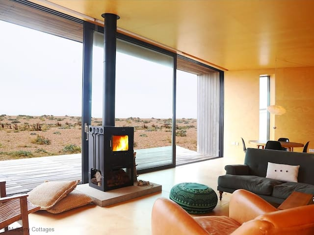 The vast poetic landscape of Dungeness is the backdrop for this stunning designer beach house, with glorious sea views and an internal railway carriage!