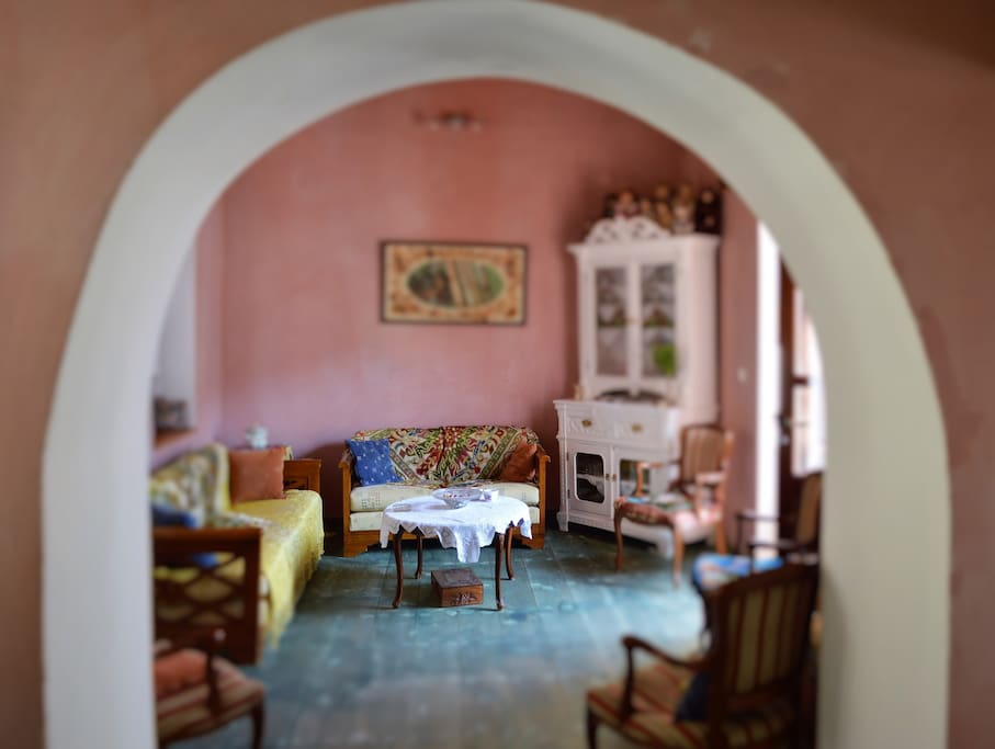 A beautiful arched wall gives access to the living room which is beautifully decorated in traditional handmade and embroidered textiles and curtains. One more person can sleep there on the three seater sofa that turns into a bed