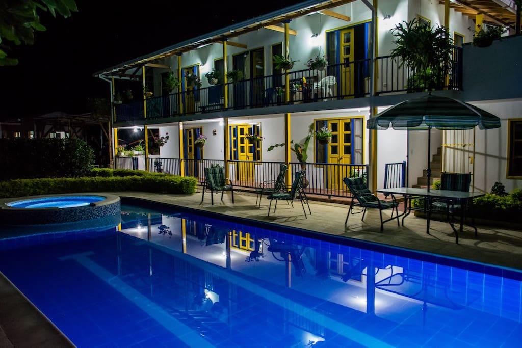 Vista nocturna de la casa principal, piscina y jacuzzi
