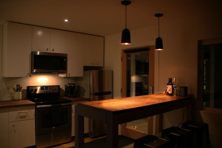 Kitchen bar warmly lit with copper pendants.