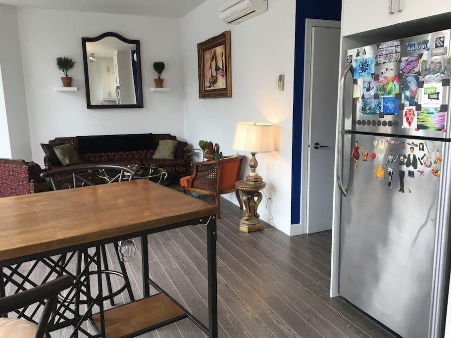 Open concept living room and kitchen. The fridge features Montreal street art.
