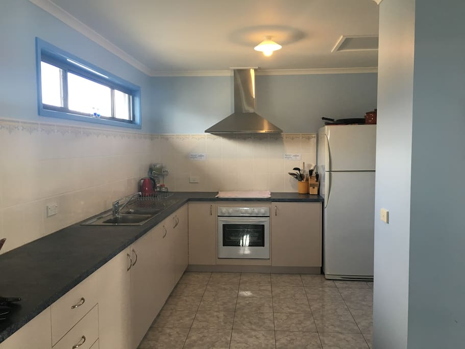 This is the kitchen.  Large refrigerator and freezer.  Cooktop, oven and griller.  A Large pantry and cupboard space for all kitchen necessities to make your experience a very pleasant one.