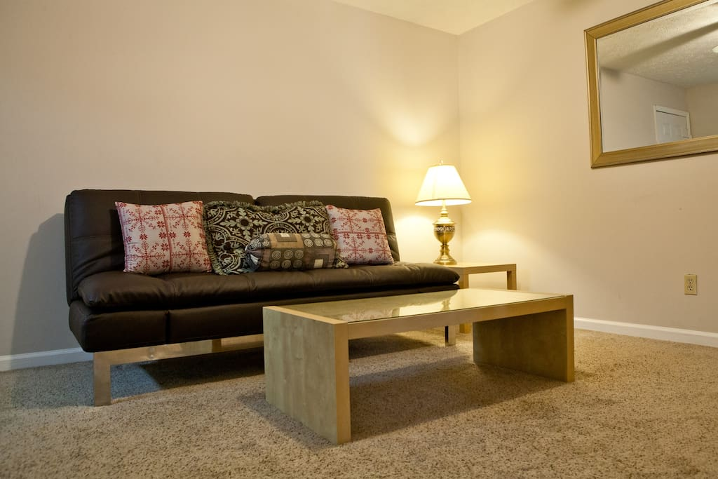Living area with futon, lamps, and coffee table.