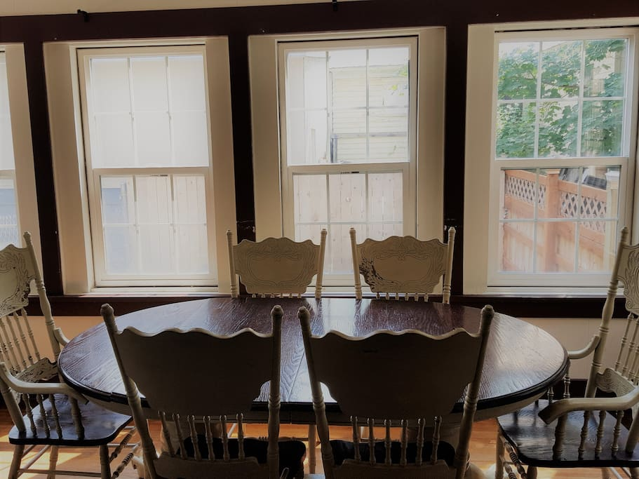 Large dining table seats six in the light filled sun room