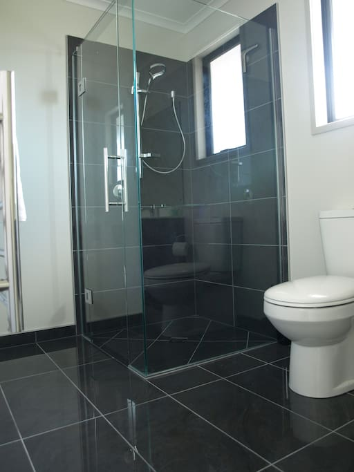 The tiled floor glass shower with an amazing shower head that drenches you.